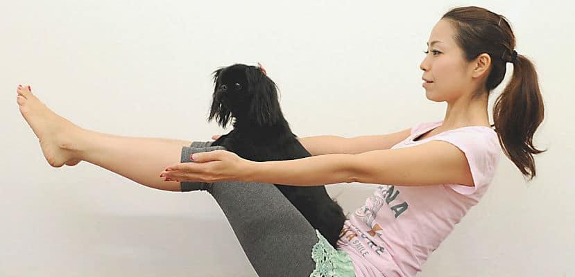 Mujer practicando Yoga con su perro.