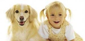 Niña junto a un perro.