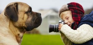 Niño fotografiando a un perro.