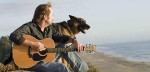 Hombre tocando la guitarra junto a su perro.