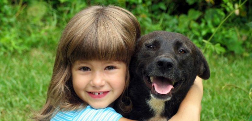Niña abrazando a un perro.