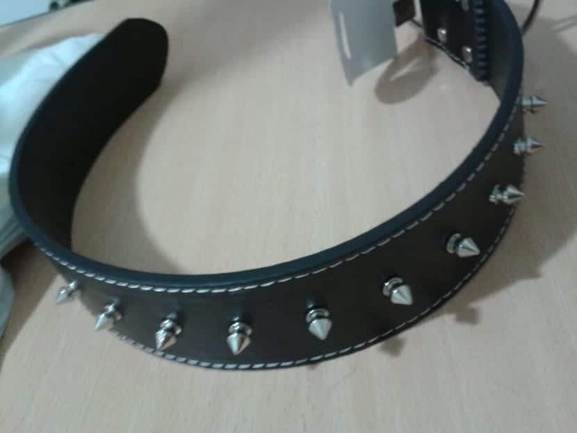 Collar negro con puas para perro encima de una mesa