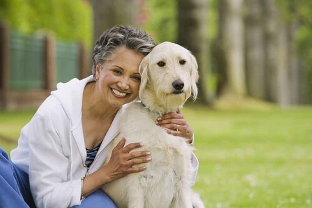 persona mauor muy sonriente abrazando a un perro
